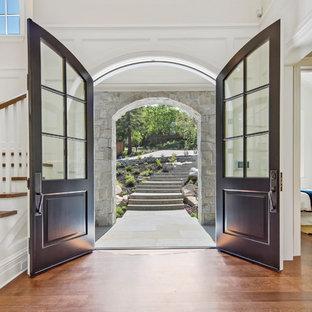 Esempio di una grande porta d'ingresso tradizionale con pareti bianche, pavimento in legno massello medio, una porta a due ante, una porta nera e pavimento marrone