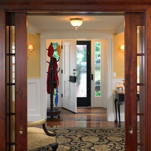 Entryway - mid-sized coastal medium tone wood floor entryway idea in Boston with yellow walls and a white front door