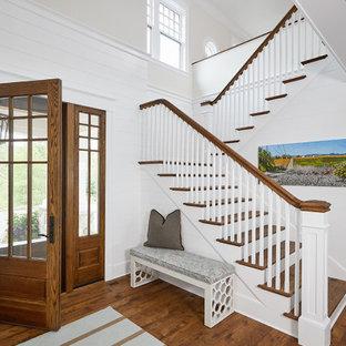 На фото: большое фойе в морском стиле с белыми стенами, паркетным полом среднего тона, одностворчатой входной дверью, входной дверью из дерева среднего тона, коричневым полом и стенами из вагонки