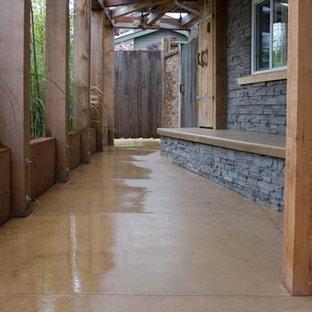Идея дизайна: узкая прихожая среднего размера в стиле фьюжн с оранжевыми стенами, бетонным полом, одностворчатой входной дверью и входной дверью из светлого дерева