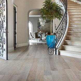 Aménagement d'un hall d'entrée classique de taille moyenne avec un mur gris, un sol en bois brun, une porte simple, un sol beige et une porte métallisée.