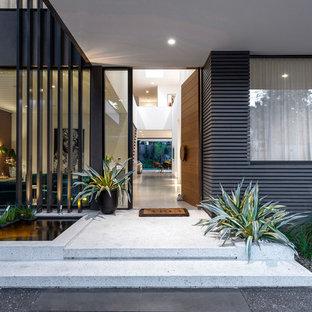 Diseño de puerta principal contemporánea, grande, con paredes blancas, suelo de cemento, puerta simple, puerta de madera en tonos medios y suelo blanco