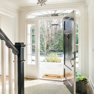 Example of a mid-sized transitional medium tone wood floor entryway design in Atlanta with white walls and a black front door