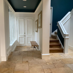 Example of a trendy travertine floor and beige floor entryway design in Seattle with blue walls and a white front door