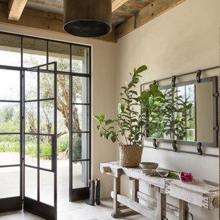 Exemple d'une entrée nature avec un mur beige, une porte simple et une porte en verre.