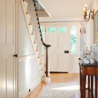 Klassisk inredning av en mellanstor hall, med en enkeldörr, en vit dörr, mellanmörkt trägolv, flerfärgade väggar och beiget golv