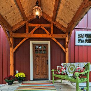Пример оригинального дизайна: входная дверь в стиле кантри с красными стенами, светлым паркетным полом, одностворчатой входной дверью и входной дверью из дерева среднего тона