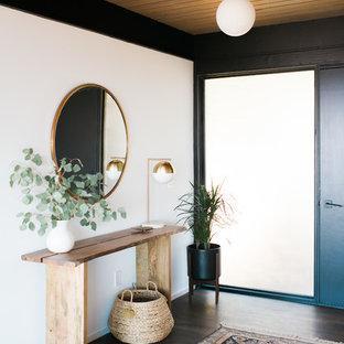 Exempel på en 60 tals foajé, med vita väggar, mörkt trägolv, en svart dörr och brunt golv