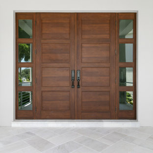 Entryway - mid-sized coastal porcelain tile, brown floor and tray ceiling entryway idea in Tampa with gray walls and a medium wood front door