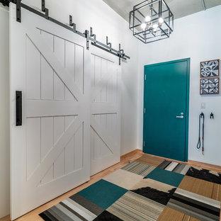 Modelo de puerta principal industrial, de tamaño medio, con paredes blancas, suelo de madera clara, puerta simple, puerta azul y suelo marrón