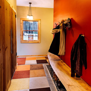 Foto di un grande ingresso stile rurale con pareti rosse, pavimento in cemento, pavimento grigio, una porta singola e una porta bianca