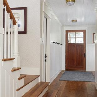 Idee per un piccolo ingresso costiero con pareti multicolore, pavimento in legno massello medio, una porta singola, una porta in legno bruno e pavimento marrone