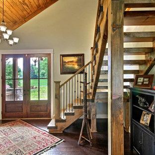 Exempel på en mellanstor amerikansk ingång och ytterdörr, med beige väggar, mörkt trägolv, en dubbeldörr, mörk trädörr och brunt golv