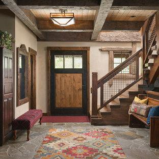 ジャクソンの中サイズの片開きドアラスティックスタイルのおしゃれな玄関ドア (ベージュの壁、スレートの床、木目調のドア、グレーの床) の写真