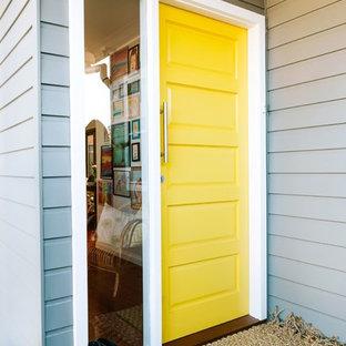 Idee per una porta d'ingresso contemporanea con pareti blu, pavimento in legno massello medio, una porta singola, una porta gialla e pavimento marrone