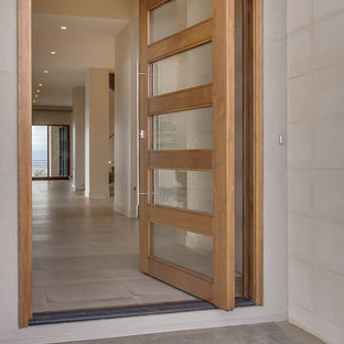 Example of a mid-sized transitional concrete floor and beige floor entryway design in Denver with beige walls and a glass front door