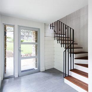 Foto di una porta d'ingresso tradizionale di medie dimensioni con pareti bianche, pavimento in gres porcellanato, una porta singola e una porta in metallo