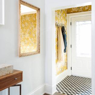 トロントの小さい片開きドアエクレクティックスタイルのおしゃれな玄関ラウンジ (マルチカラーの壁、無垢フローリング、白いドア、茶色い床) の写真