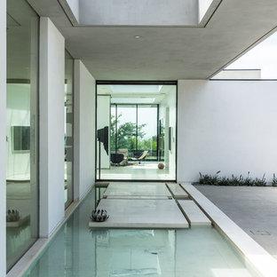 Geräumige Moderne Haustür mit weißer Wandfarbe, Porzellan-Bodenfliesen, Drehtür und Glastür in Los Angeles