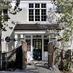 На фото: входная дверь в классическом стиле с одностворчатой входной дверью и зеленой входной дверью