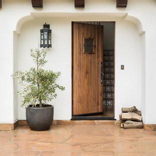 Foto de puerta principal mediterránea con paredes blancas, puerta simple, puerta de madera en tonos medios y suelo naranja