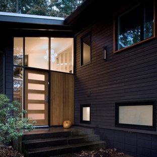 Esempio di una porta d'ingresso minimalista di medie dimensioni con una porta singola, una porta in vetro e pareti bianche
