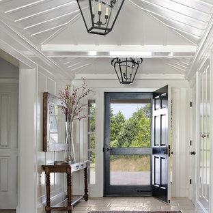 Esempio di un ingresso o corridoio in campagna con pareti bianche, una porta singola e una porta nera
