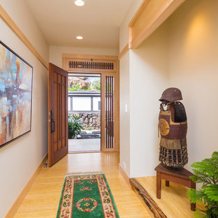 Inspiration for a mid-sized zen light wood floor entryway remodel in Hawaii with white walls and a medium wood front door