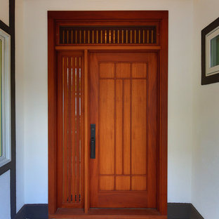 Inspiration for an asian porcelain floor entryway remodel in Hawaii with white walls and a medium wood front door