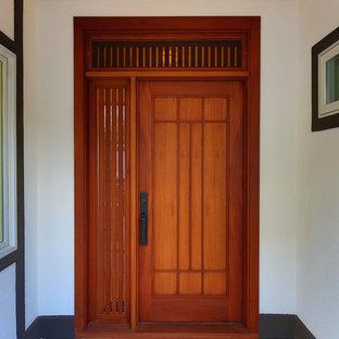 Foto di una porta d'ingresso etnica con pareti bianche, pavimento in gres porcellanato, una porta singola e una porta in legno bruno