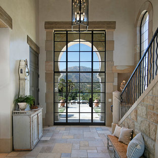 Inspiration for a mediterranean beige floor entryway remodel in Santa Barbara with white walls and a glass front door