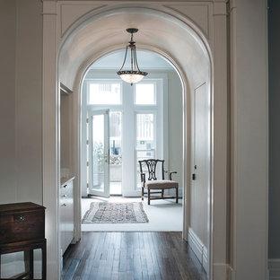 Immagine di un ingresso chic con pareti grigie, parquet scuro, una porta singola, una porta in vetro e pavimento marrone