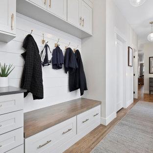Cette image montre une entrée traditionnelle avec un vestiaire, un mur blanc, un sol marron et du lambris de bois.