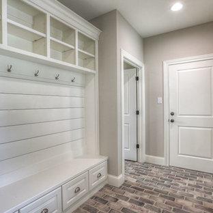 ヒューストンの中くらいの片開きドアトランジショナルスタイルのおしゃれなマッドルーム (ベージュの壁、レンガの床、白いドア、ベージュの床) の写真