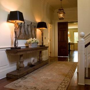 Cette image montre un hall d'entrée traditionnel de taille moyenne avec un mur jaune et un sol en bois brun.