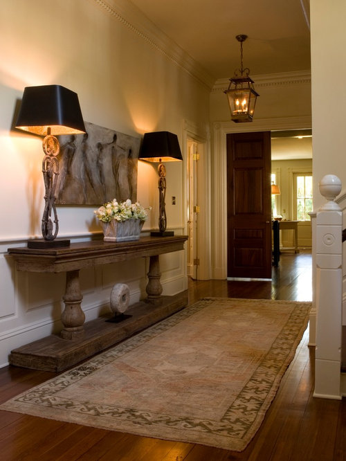 furniture for the foyer. example of a midsized classic medium tone wood floor foyer design in charleston with furniture for the