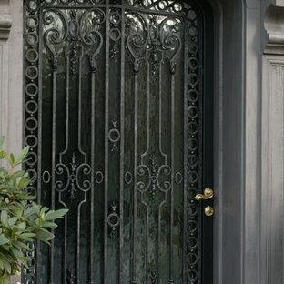 Immagine di una grande porta d'ingresso tradizionale con pavimento in pietra calcarea, una porta singola e una porta in vetro