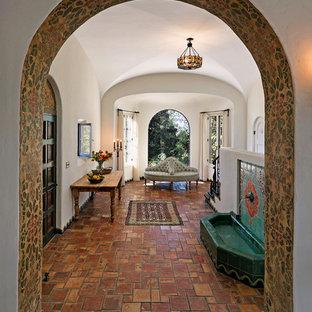 Foto di un ampio ingresso mediterraneo con pareti bianche, pavimento in terracotta e una porta singola