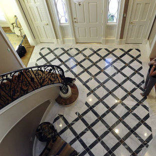 Example of a large classic marble floor entryway design in Other with beige walls and a white front door