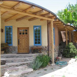 アルバカーキの小さい片開きドアサンタフェスタイルのおしゃれな玄関ドア (木目調のドア) の写真