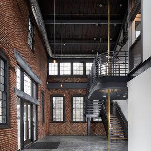 Cette image montre une très grand entrée urbaine avec sol en stratifié, une porte double, une porte en verre, un sol gris, un plafond en poutres apparentes et un mur en parement de brique.