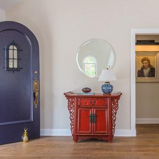 Inspiration för stora klassiska ingångspartier, med beige väggar, mellanmörkt trägolv, en enkeldörr, en lila dörr och brunt golv
