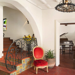 Tuscan terra-cotta floor and red floor foyer photo in Los Angeles