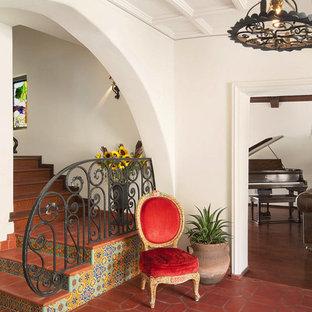Idée de décoration pour un hall d'entrée méditerranéen avec un sol en carreau de terre cuite et un sol rouge.