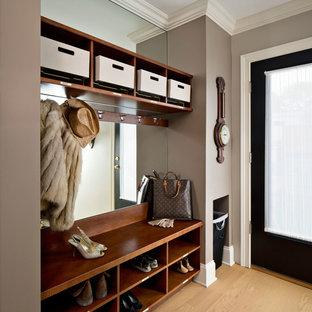 Exemple d'une entrée chic de taille moyenne avec un vestiaire, un mur violet et un sol en bois clair.
