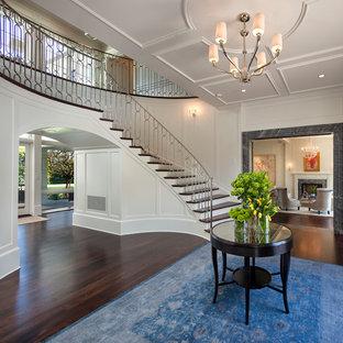Elegant dark wood floor and brown floor foyer photo in Los Angeles with white walls