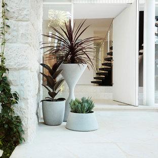 Esempio di una porta d'ingresso moderna con pareti bianche, una porta a pivot, una porta bianca e pavimento bianco