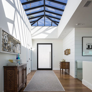 Новые идеи обустройства дома: узкая прихожая в современном стиле с белыми стенами, паркетным полом среднего тона, поворотной входной дверью, стеклянной входной дверью и коричневым полом