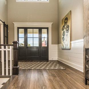 Пример оригинального дизайна: входная дверь в стиле модернизм с бежевыми стенами, паркетным полом среднего тона, двустворчатой входной дверью и входной дверью из темного дерева