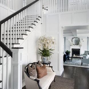 Foto di un grande corridoio chic con pareti bianche, parquet scuro, pavimento marrone e boiserie